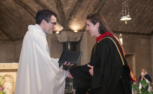 The 2015 recipient of the Susan M. Shaughnessy Award, Caroline Bernard, receives the award certificate from Fr. Lopez.